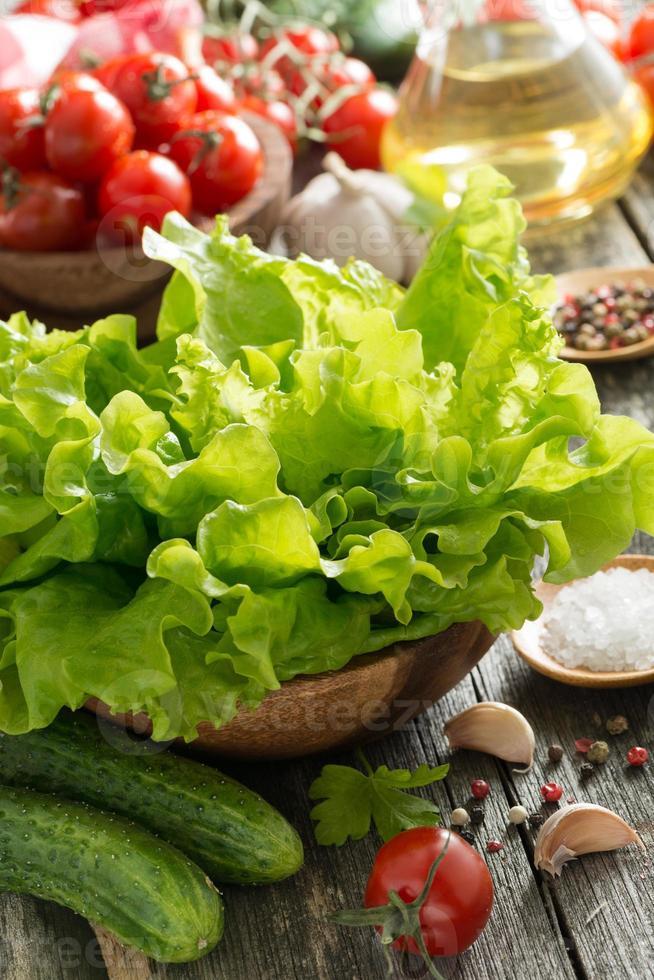 Schüssel mit frischem grünem Salat, Gemüse, Gewürzen und Olivenöl foto