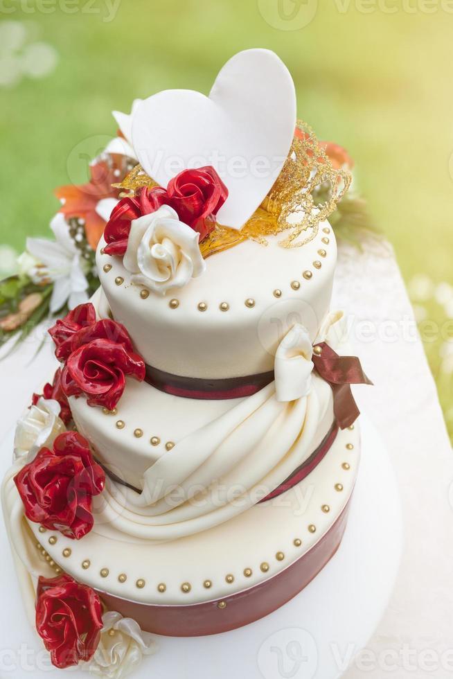 Hochzeitstorte mit essbarer Dekoration, die vom Sonnenlicht beleuchtet wird foto