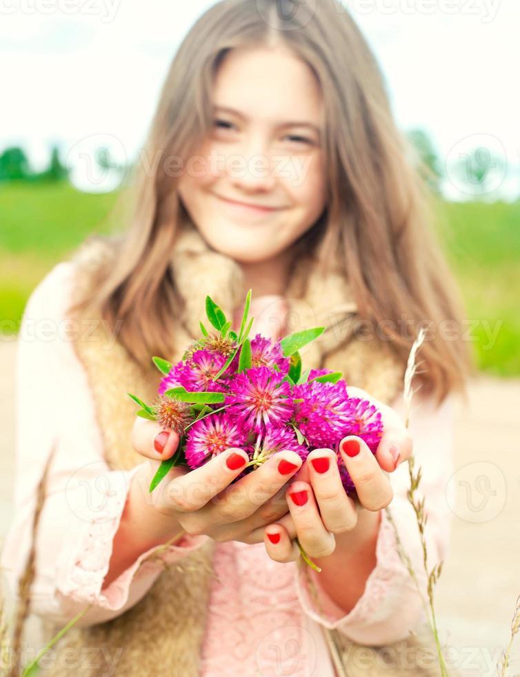 Schönheit der Natur. lächelndes junges Mädchen, das Wiesenkleeblumen hält foto