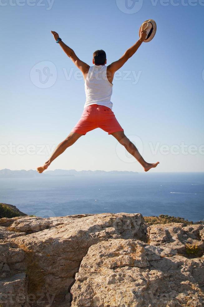 Junge mit offenen Armen springt vor Freude und feiert die Freiheit foto