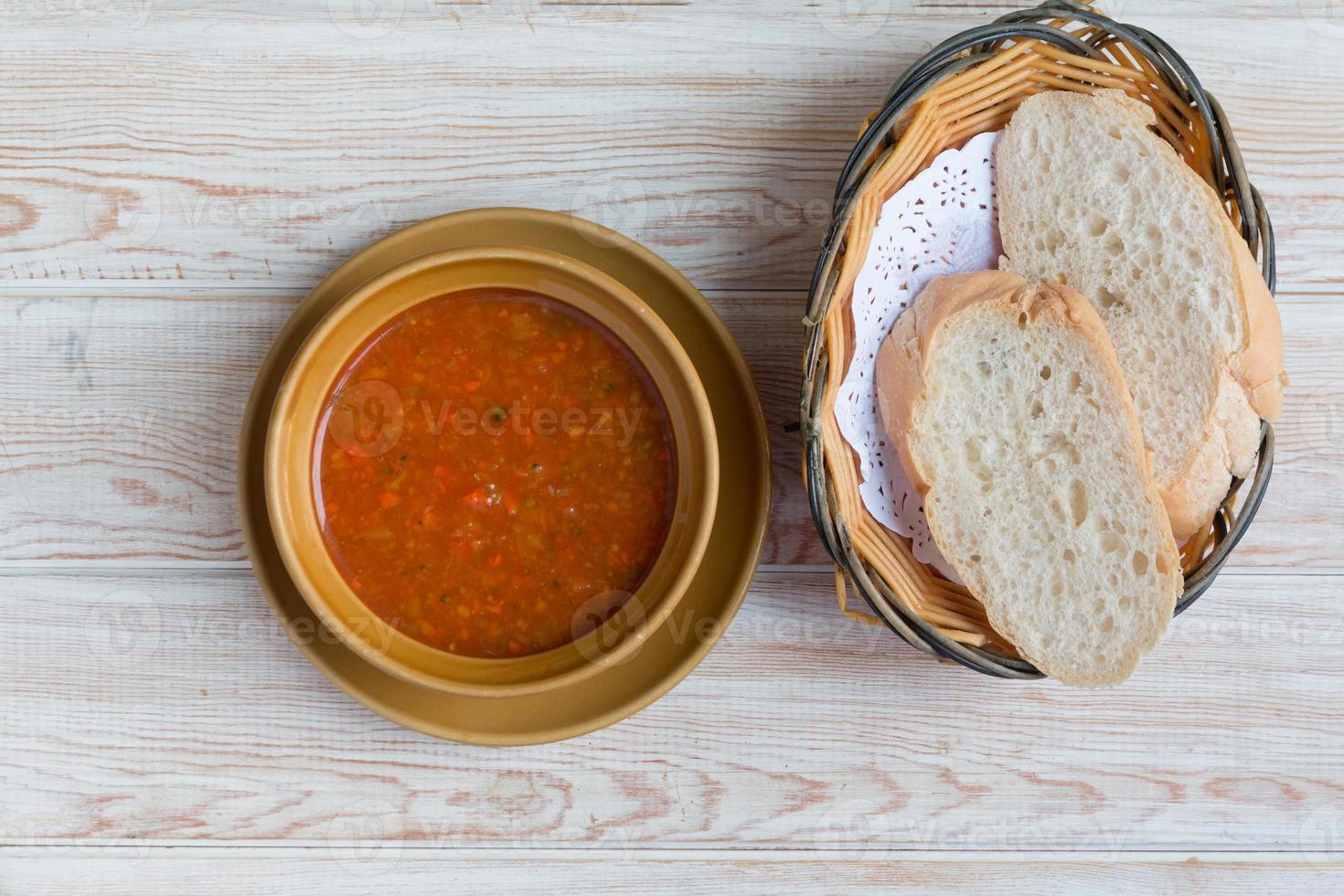 Schüssel Minestrone-Suppe mit Brot auf Holztisch foto