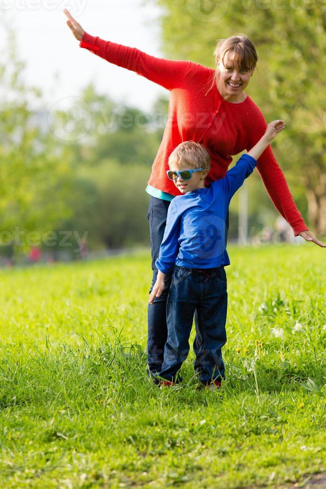 glückliche Mutter und Sohn spielen im Sommer foto