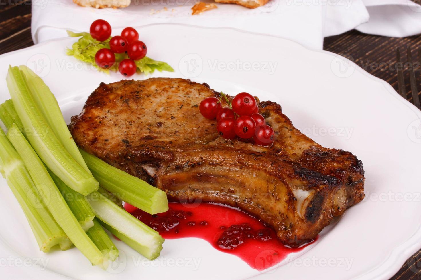 Gebratenes Schweinekotelett mit roter Johannisbeersauce und Sellerie foto