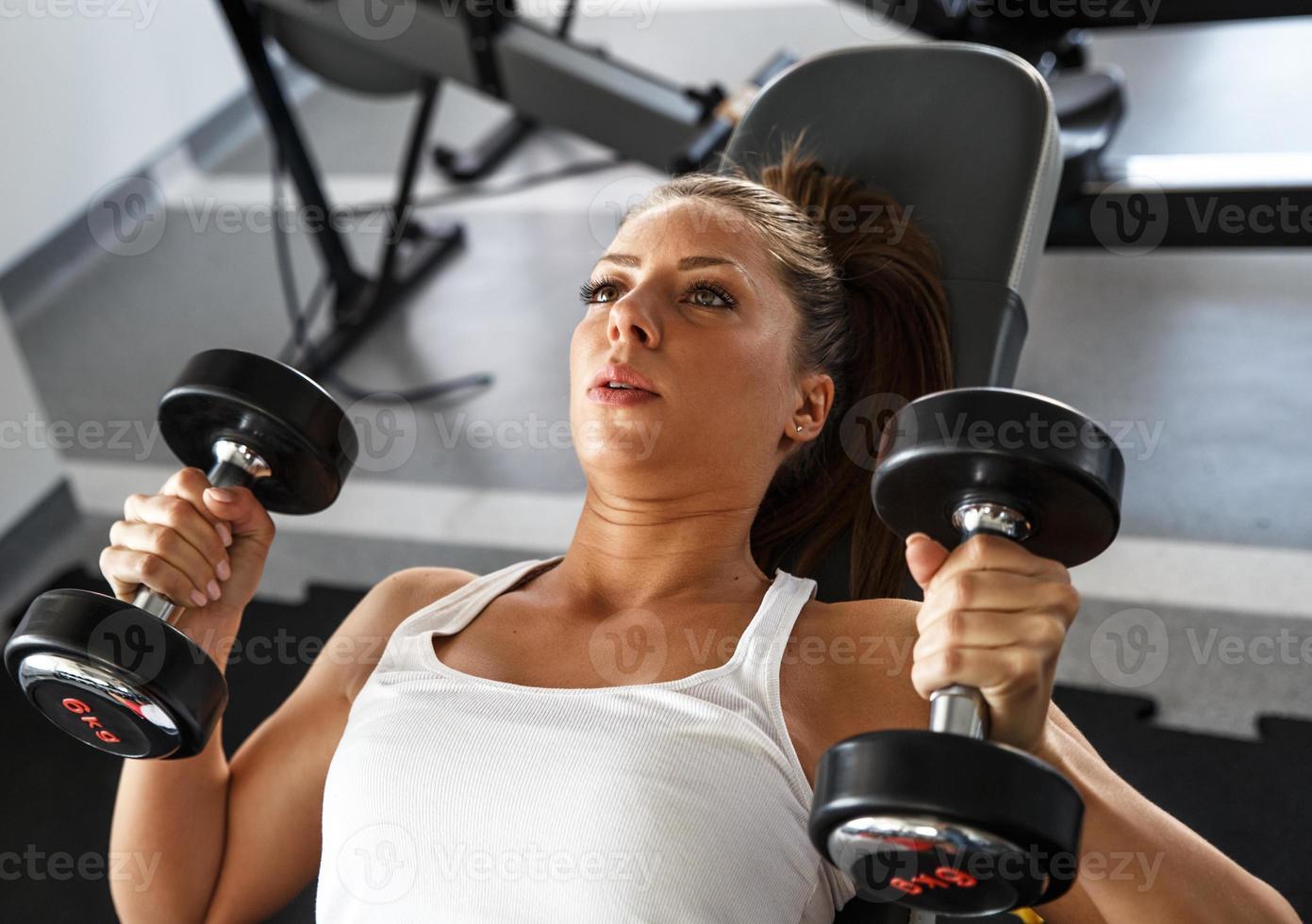 Frau, die Gewichte im Fitnessstudio hebt foto