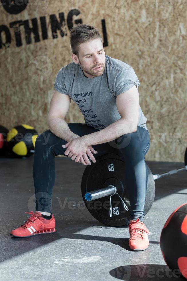 Gewichtheber sitzt auf der Langhantel foto