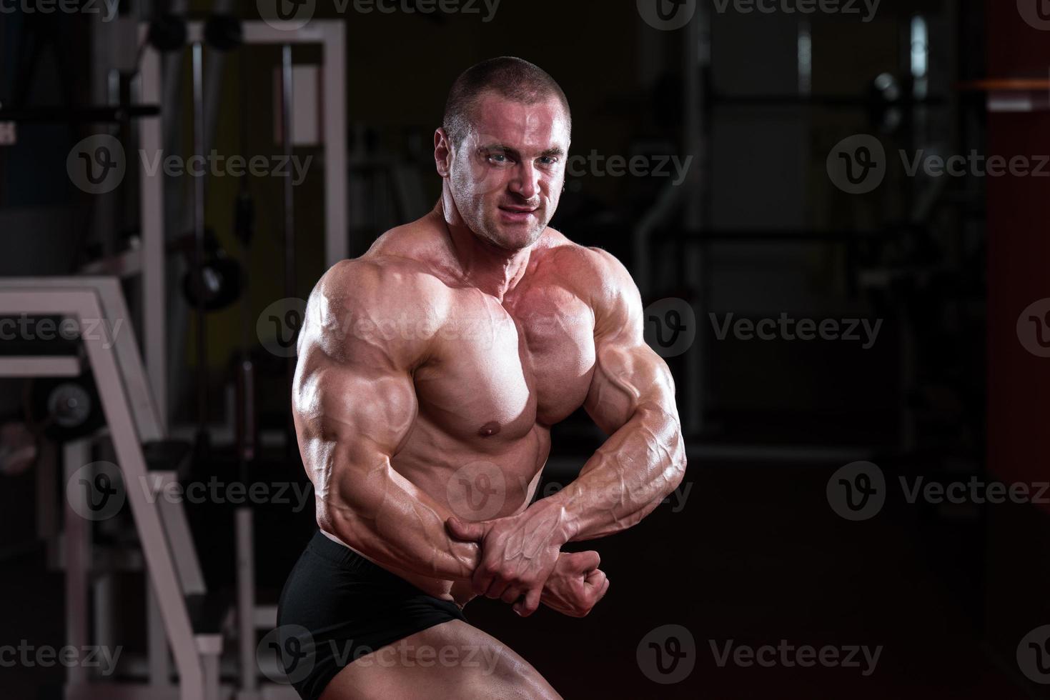 muskulöser Mann, der Muskeln spannt foto