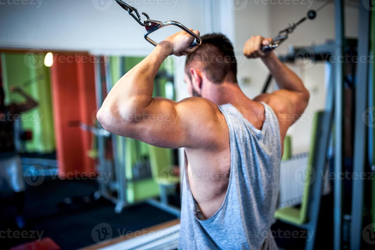 junger, muskulöser Mann, Bodybuilder, der im Fitnessstudio trainiert. Fitness con foto