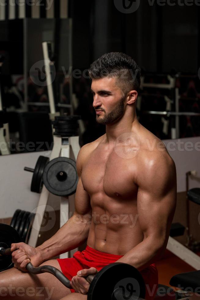 Mann, der Langhantel im Fitnessstudio hebt foto