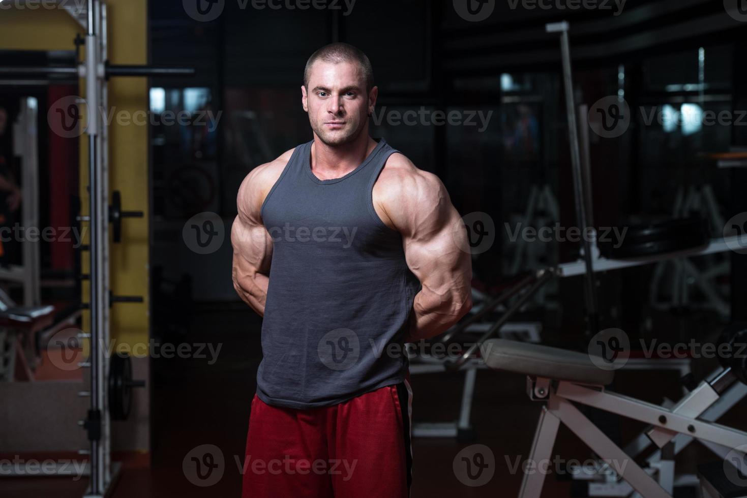 junger Bodybuilder, der Muskeln spielen lässt foto