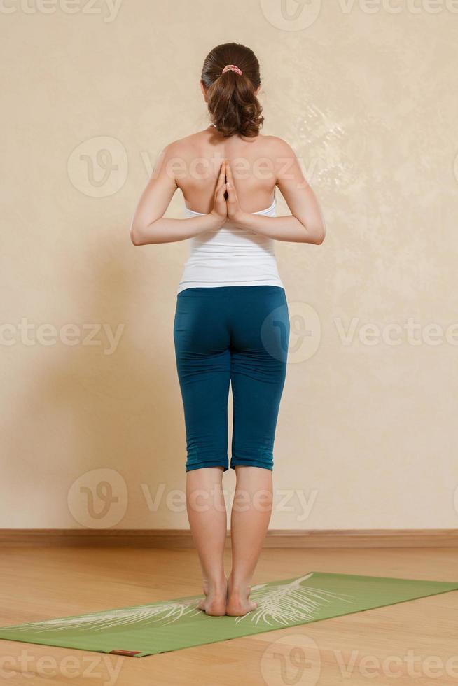 Die kaukasische Frau praktiziert Yoga im Studio foto