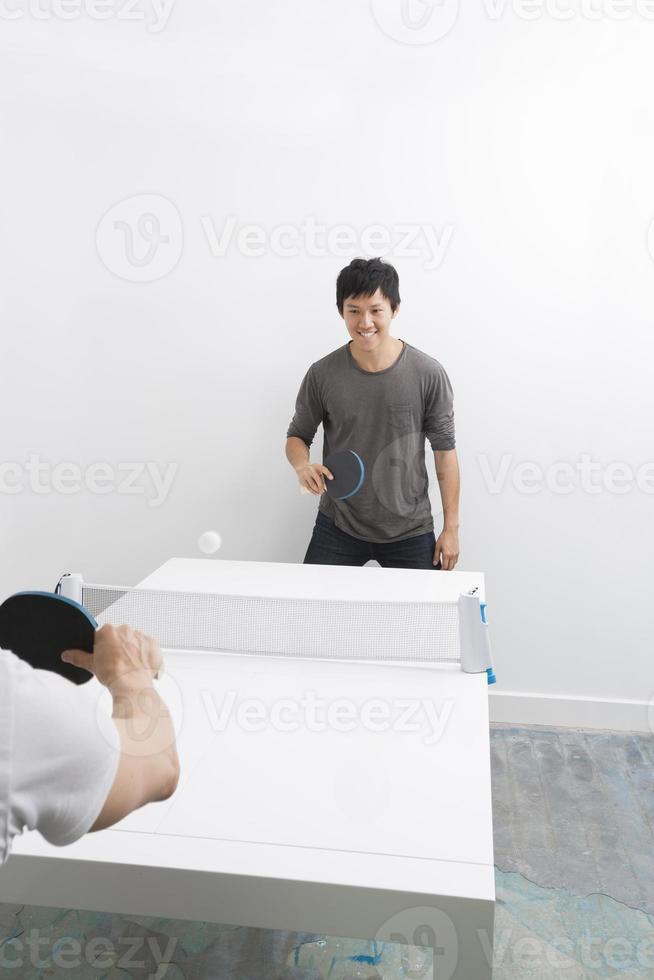 glücklicher asiatischer Mann, der Tischtennis mit Freund spielt foto