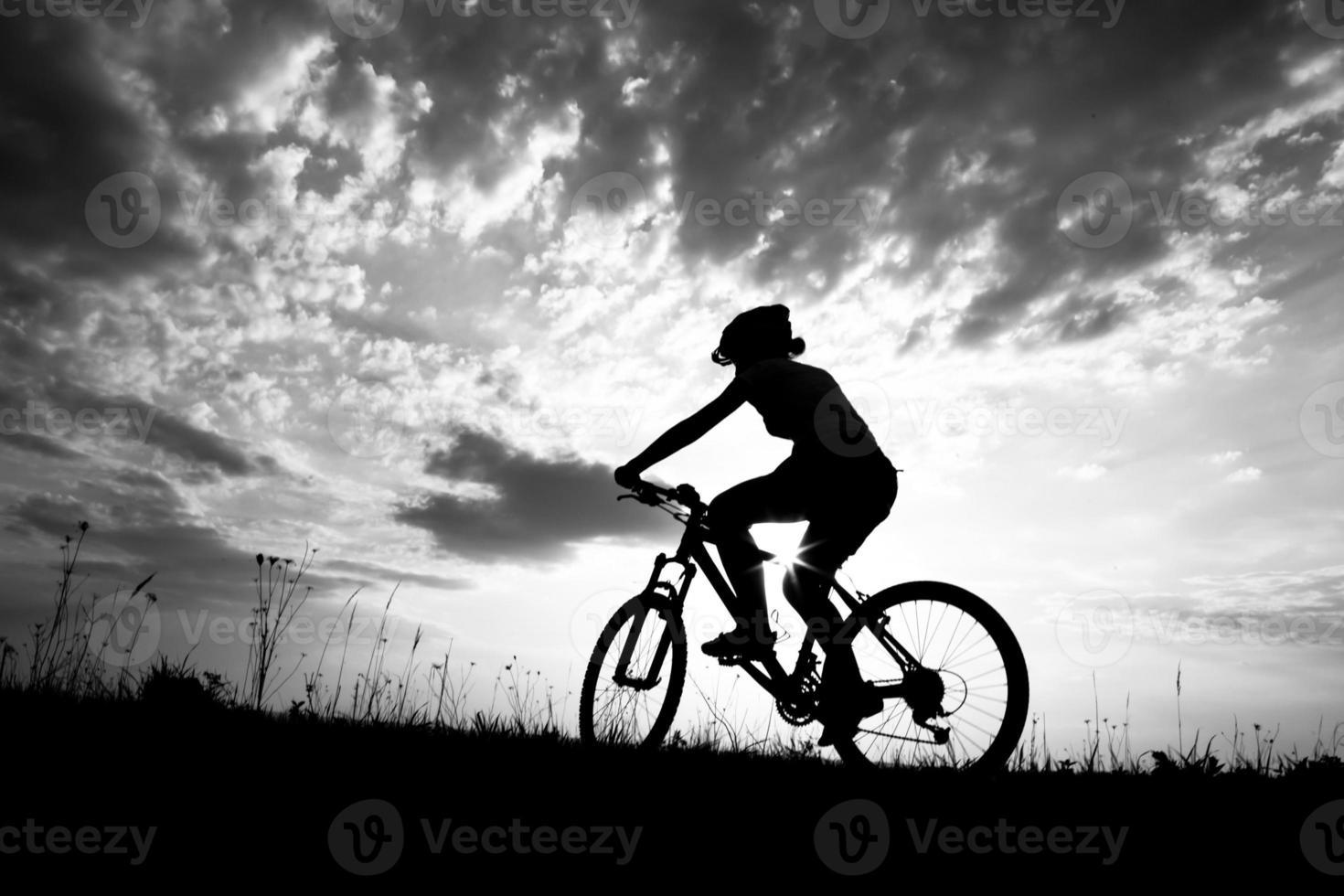 Biker-Mädchen bei Sonnenuntergang auf der Wiese foto
