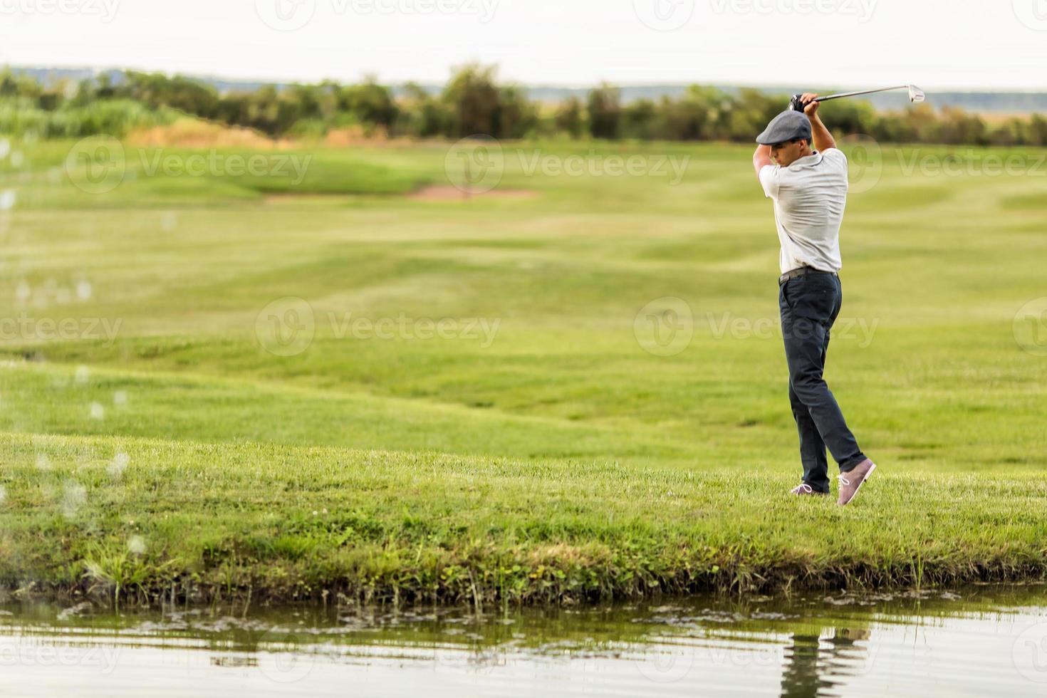 junger Mann, der Golf spielt foto