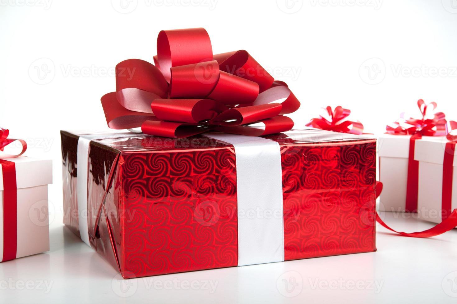eine rote Geschenkbox weiße Geschenkboxen auf grau foto