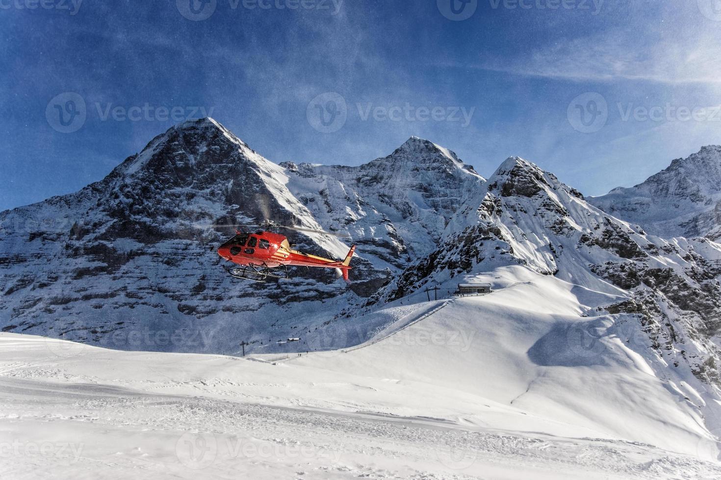 Roter Hubschrauber landet im Schweizer Skigebiet in der Nähe des Jungfrau Mountai foto