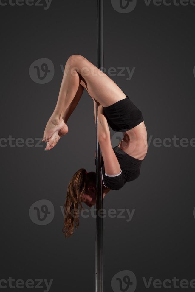Frau Übung Pole Dance auf grauem Hintergrund foto