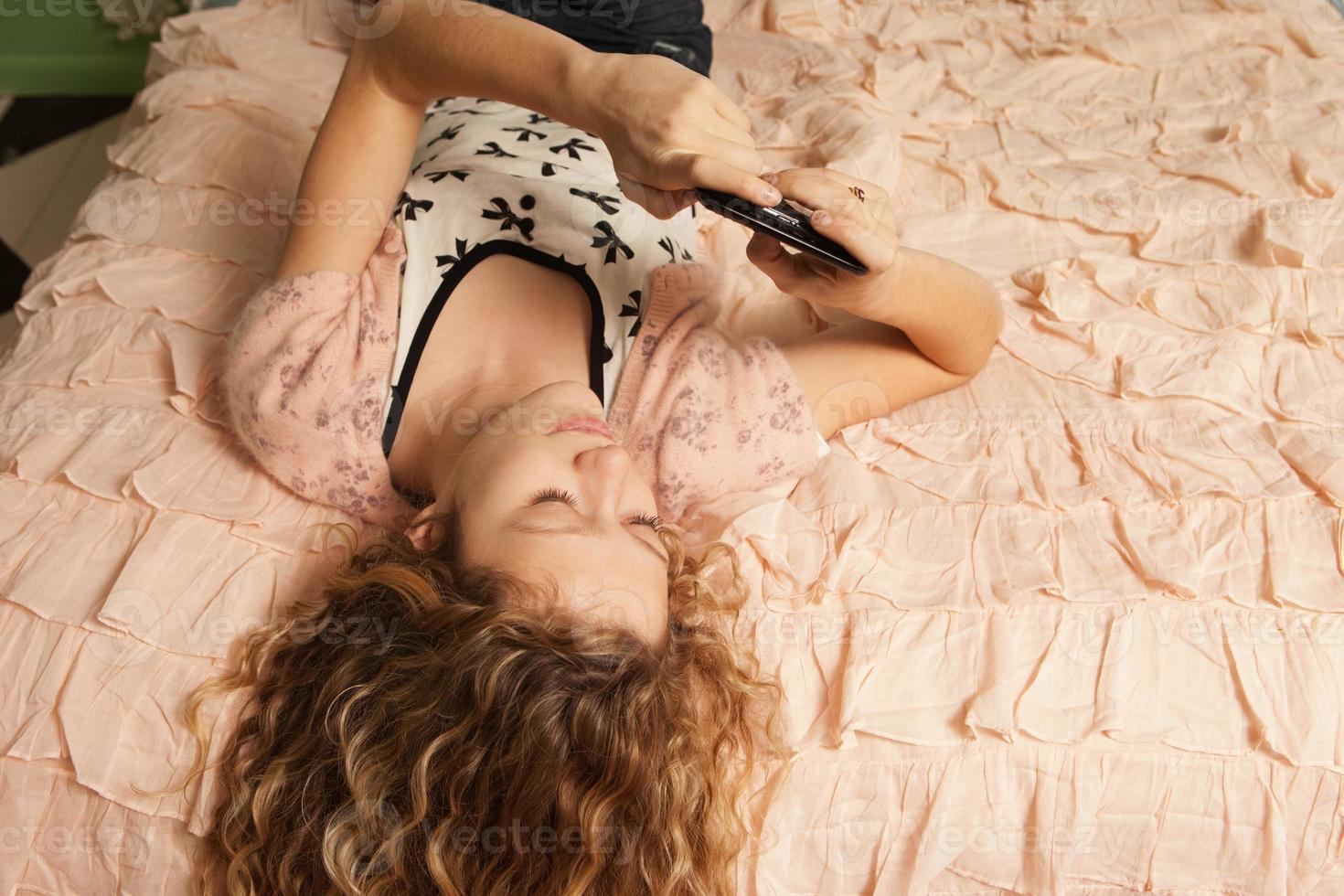 Teenager-Mädchen auf dem Bett mit Smartphone liegen foto