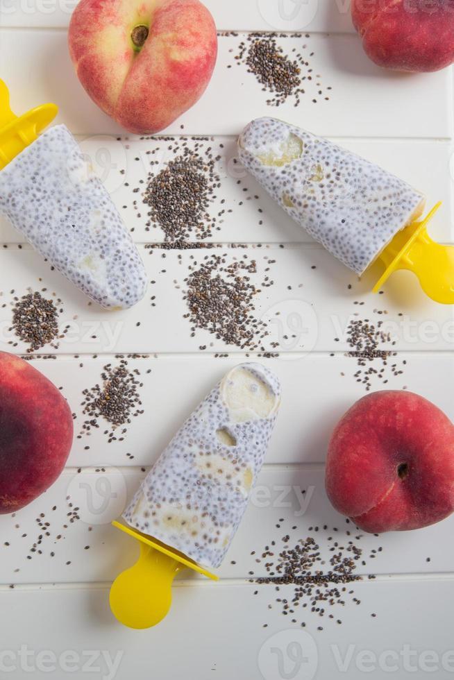 Kokos-Eis am Stiel mit Chiasamen und Pfirsich foto