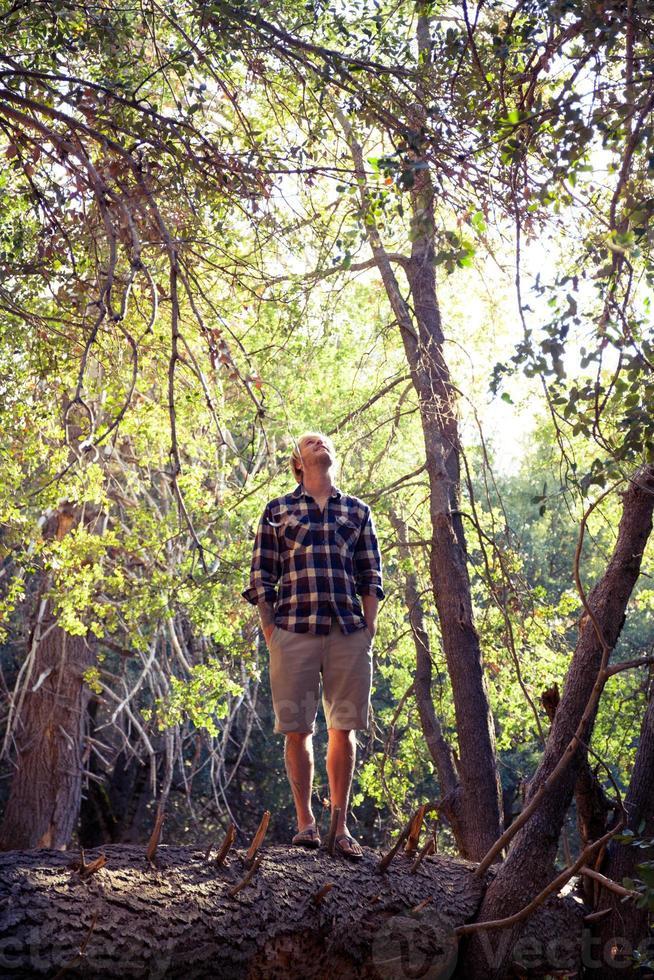 Mann auf umgestürztem Baum foto