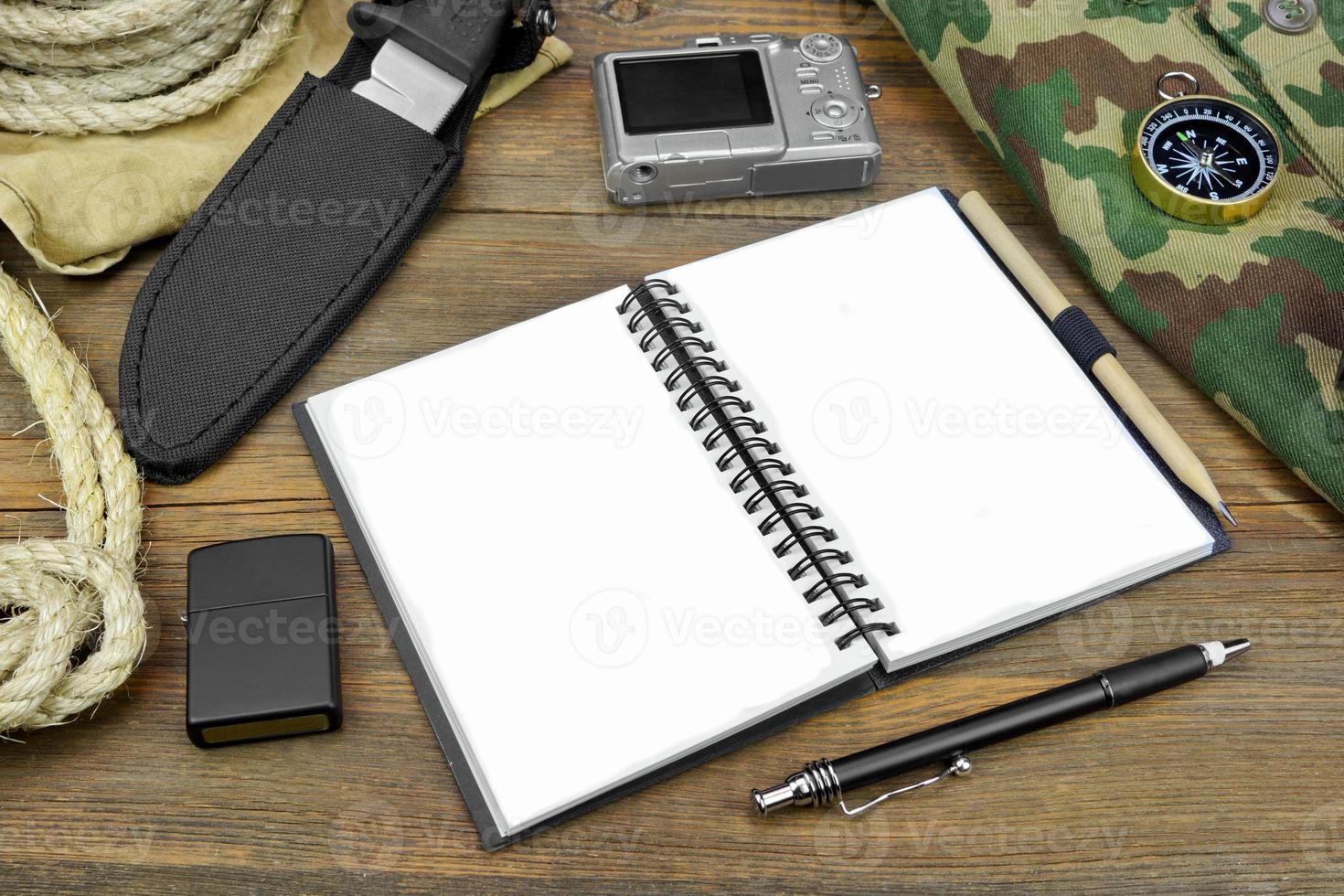 Reisevorbereitung. offenes Notizbuch, Kamera, Seil, Kompass, Stift, foto