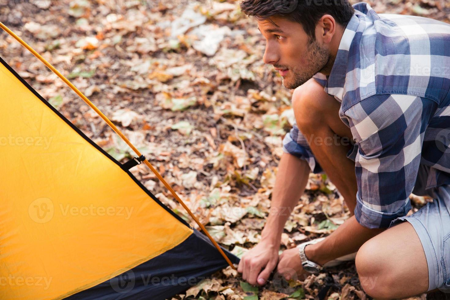 gutaussehender Mann, der ein Zelt aufbaut foto
