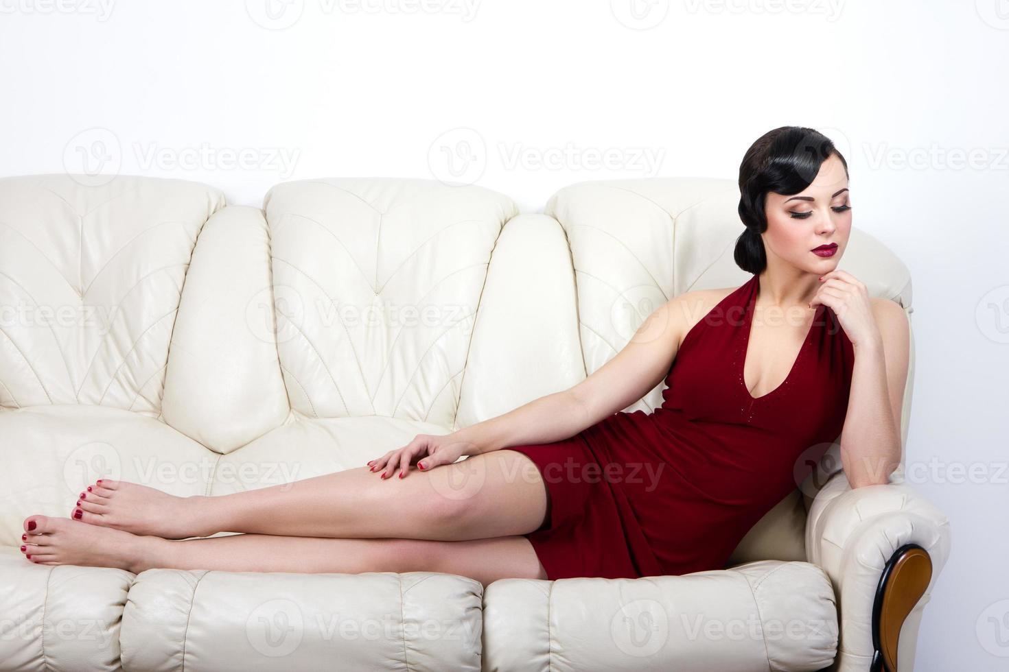 Brünette Frau im Retro-Stil, die auf dem Sofa liegt foto