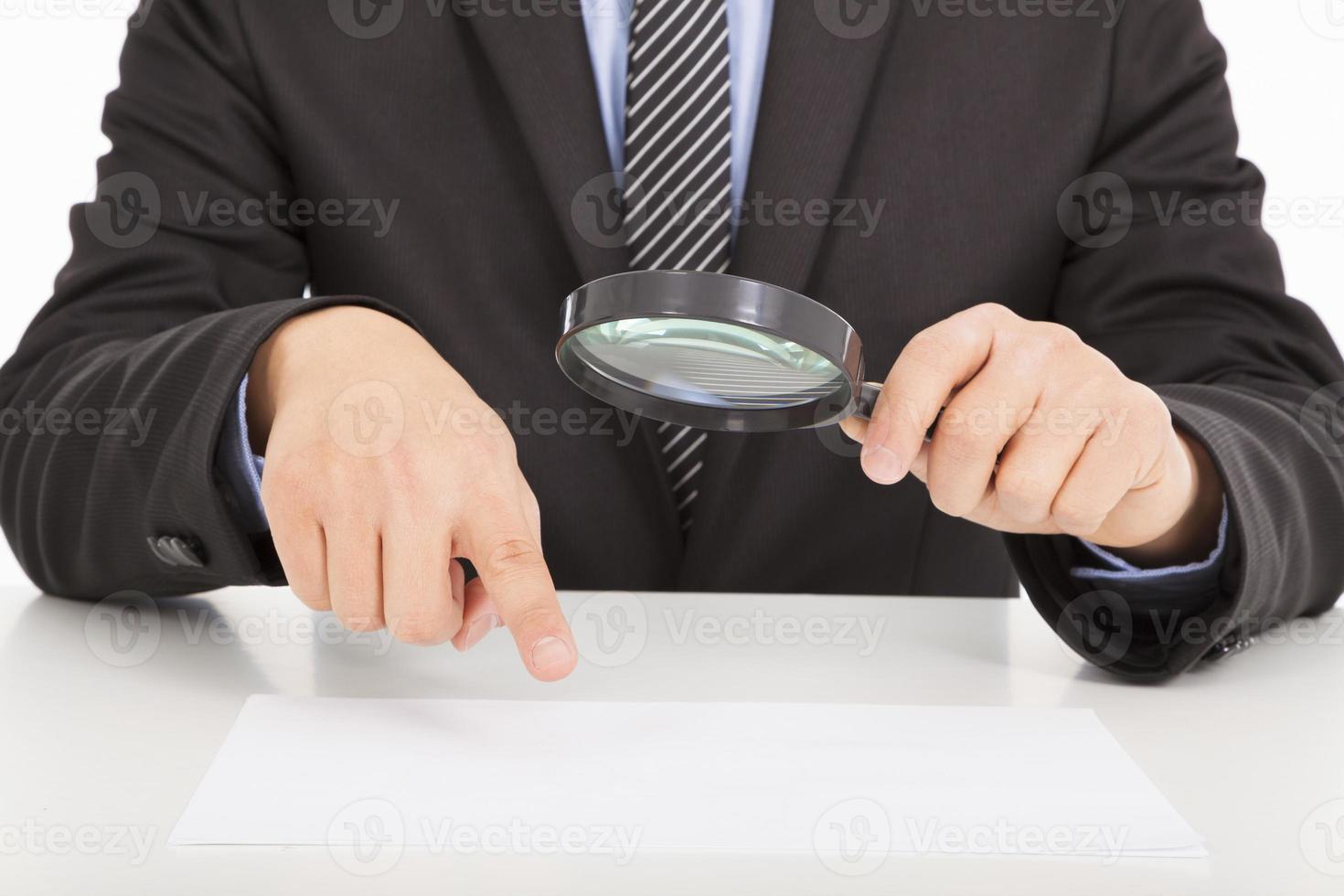 Geschäftsmann, der durch eine Lupe auf Dokumente zeigt foto