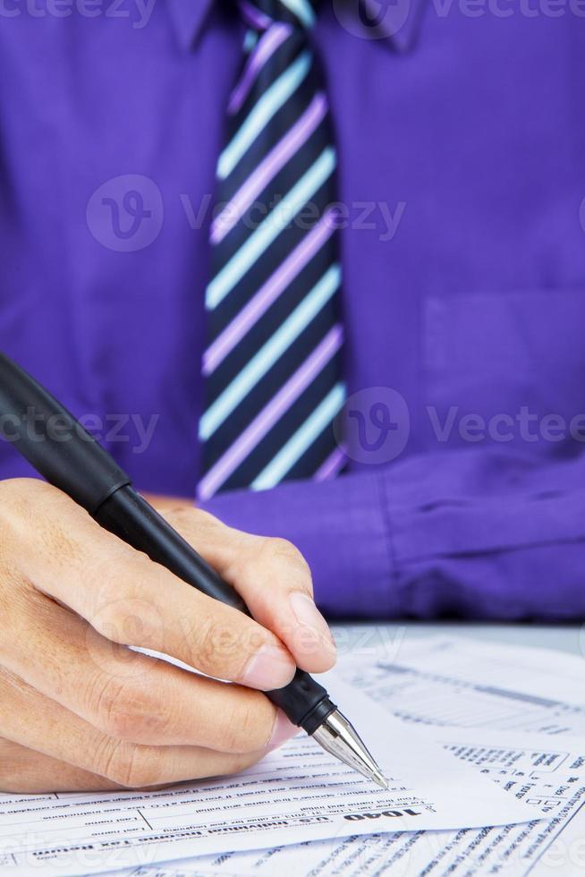 Geschäftsmann, der das Steuerformular ausfüllt foto