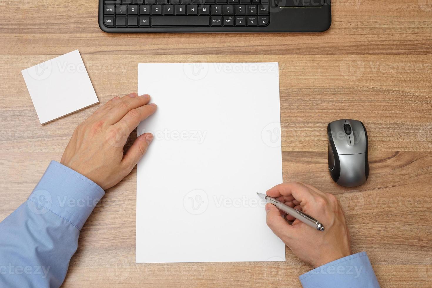 Geschäftsmann mit leerem Papier und Stift in der Hand, beginnen Sie mit dem Schreiben foto