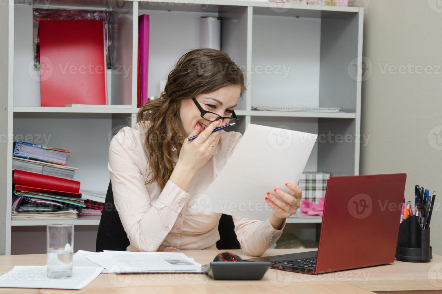 Mädchen lacht beim Lesen eines Dokuments am Arbeitsplatz foto