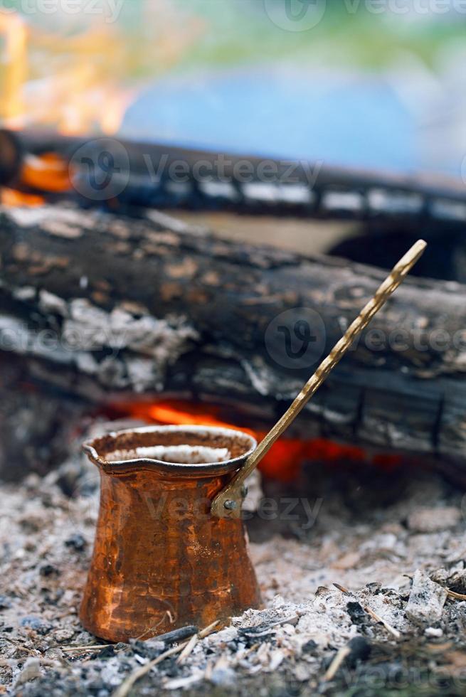 Kaffee kochen im Kamin auf Camping oder Wandern foto