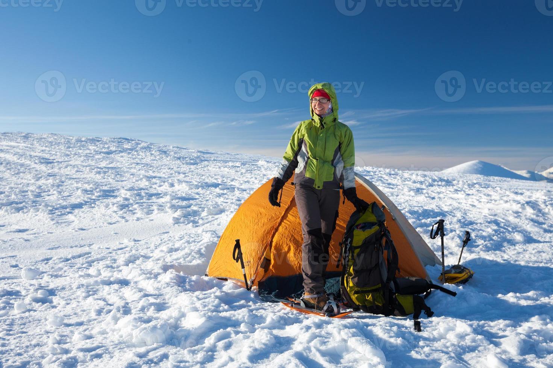 Frau, die am orange Zelt in den Winterbergen aufwirft foto