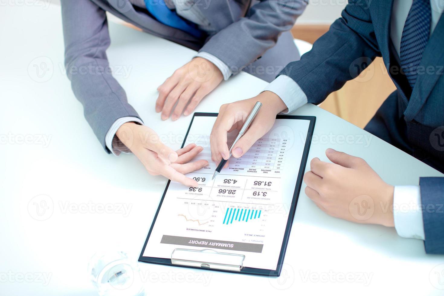 zwei Geschäftsleute, die sich einen Bericht ansehen und eine Diskussion führen foto