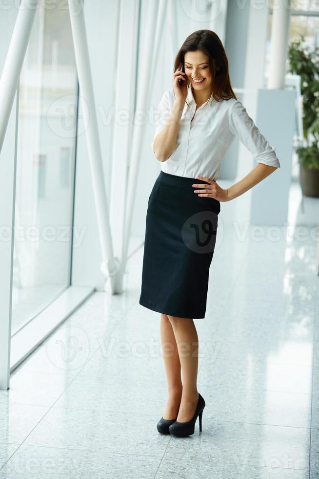junge Geschäftsfrau, die auf dem Handy spricht foto