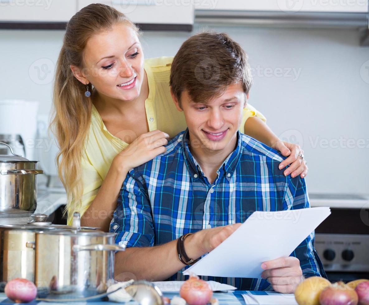 glückliche Paare, die Formulare für gemeinsames Bankwesen ausfüllen foto
