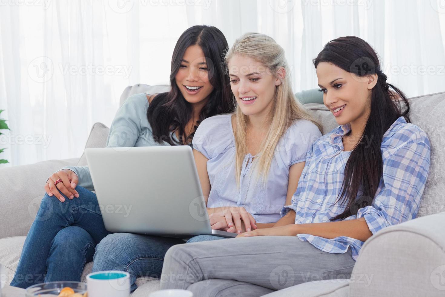 lächelnde Freunde, die zusammen Laptop betrachten foto