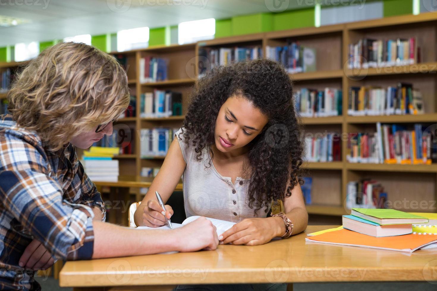 Studenten, die zusammen in der Bibliothek studieren foto