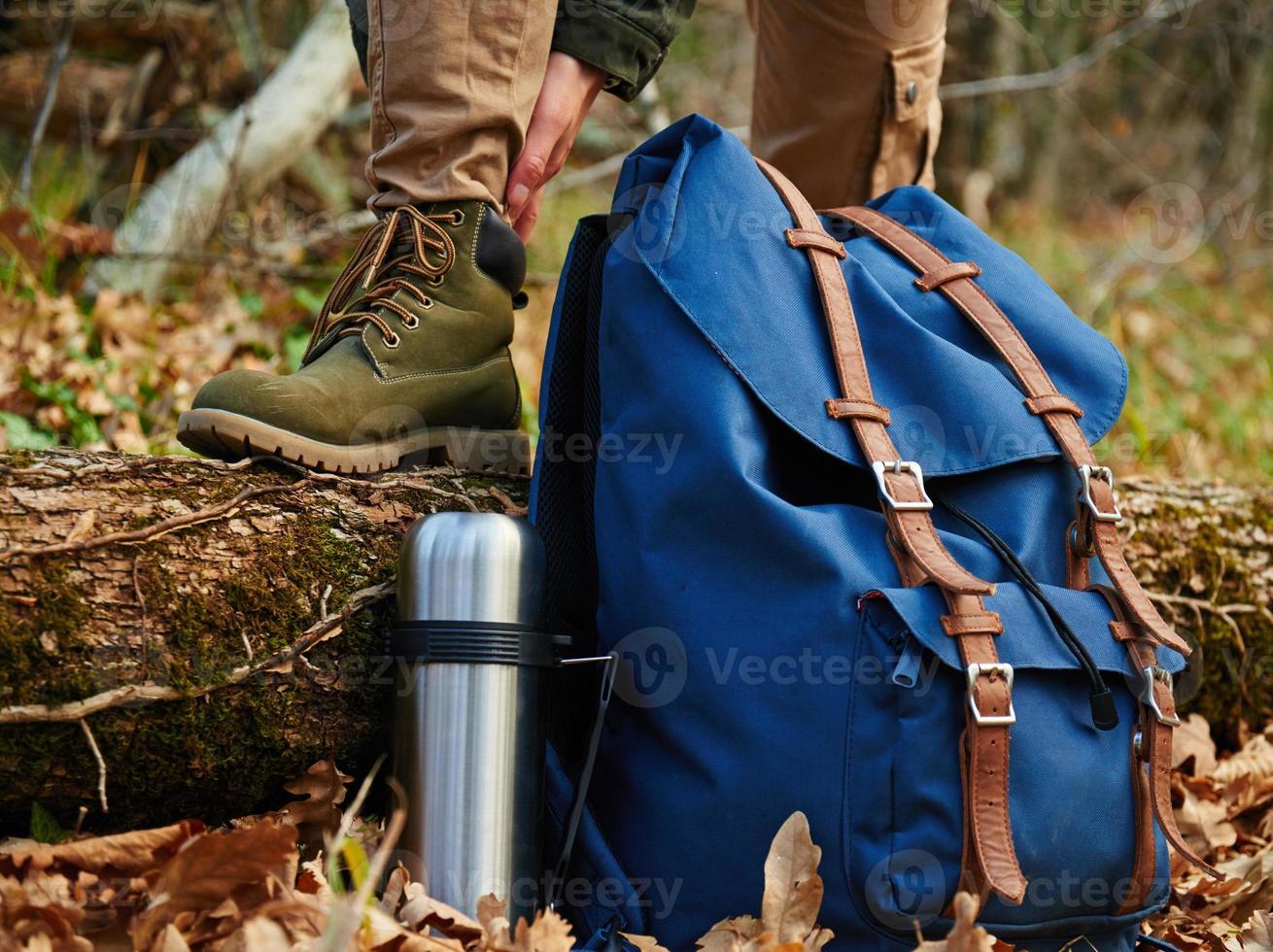 Wanderer zieht Stiefel im Freien an, Blick auf die Beine foto