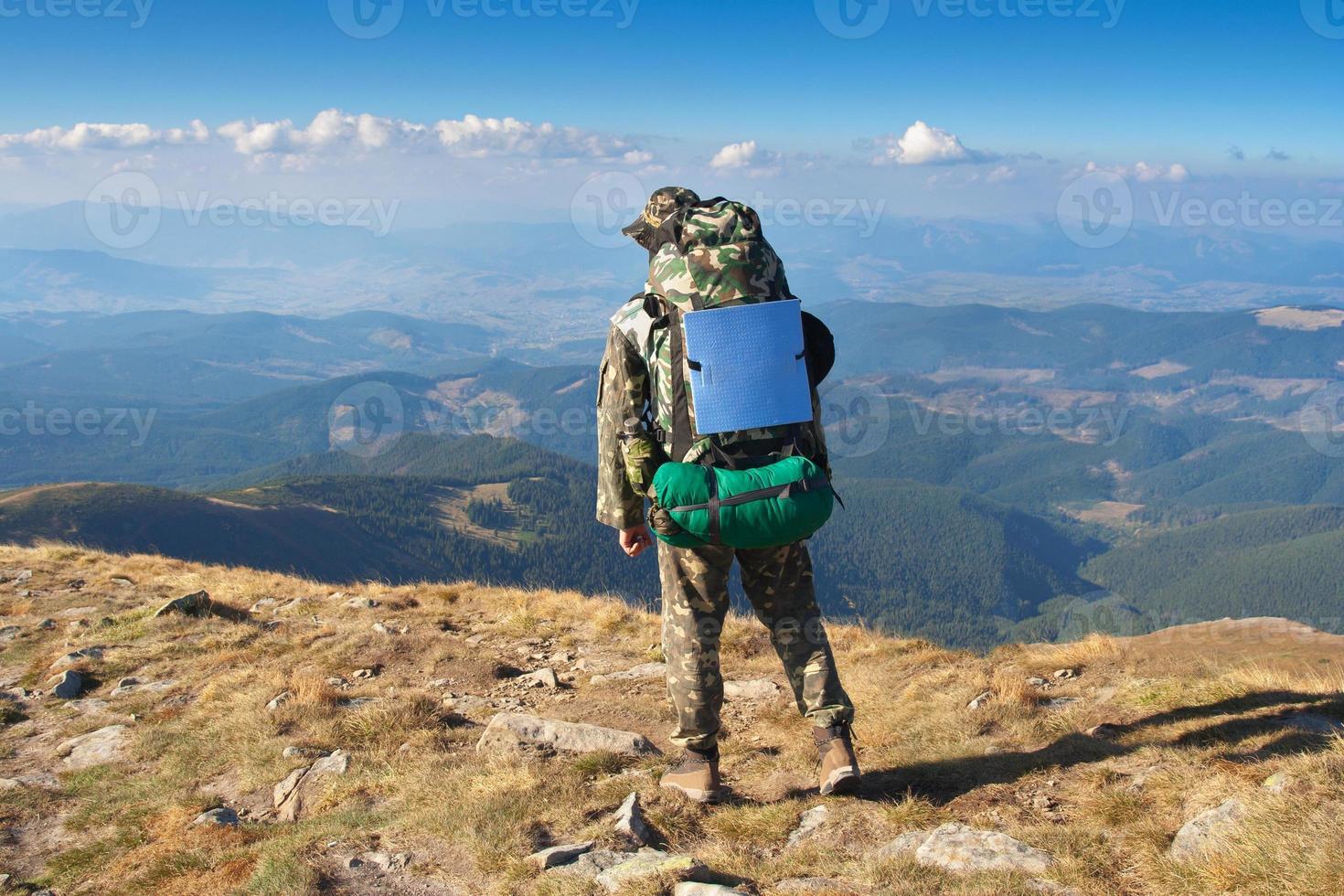 männlicher Wanderer steht auf einem Berggipfel foto