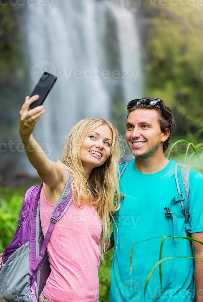 Paar hat Spaß beim gemeinsamen Fotografieren im Freien auf einer Wanderung foto