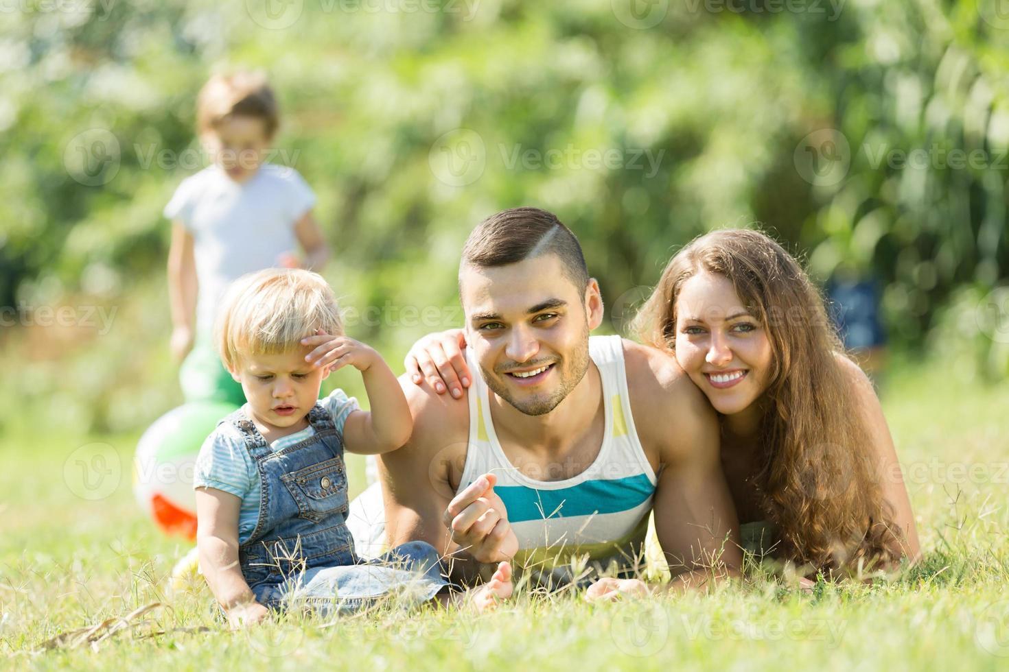 Eltern mit Kindern im Gras liegen foto