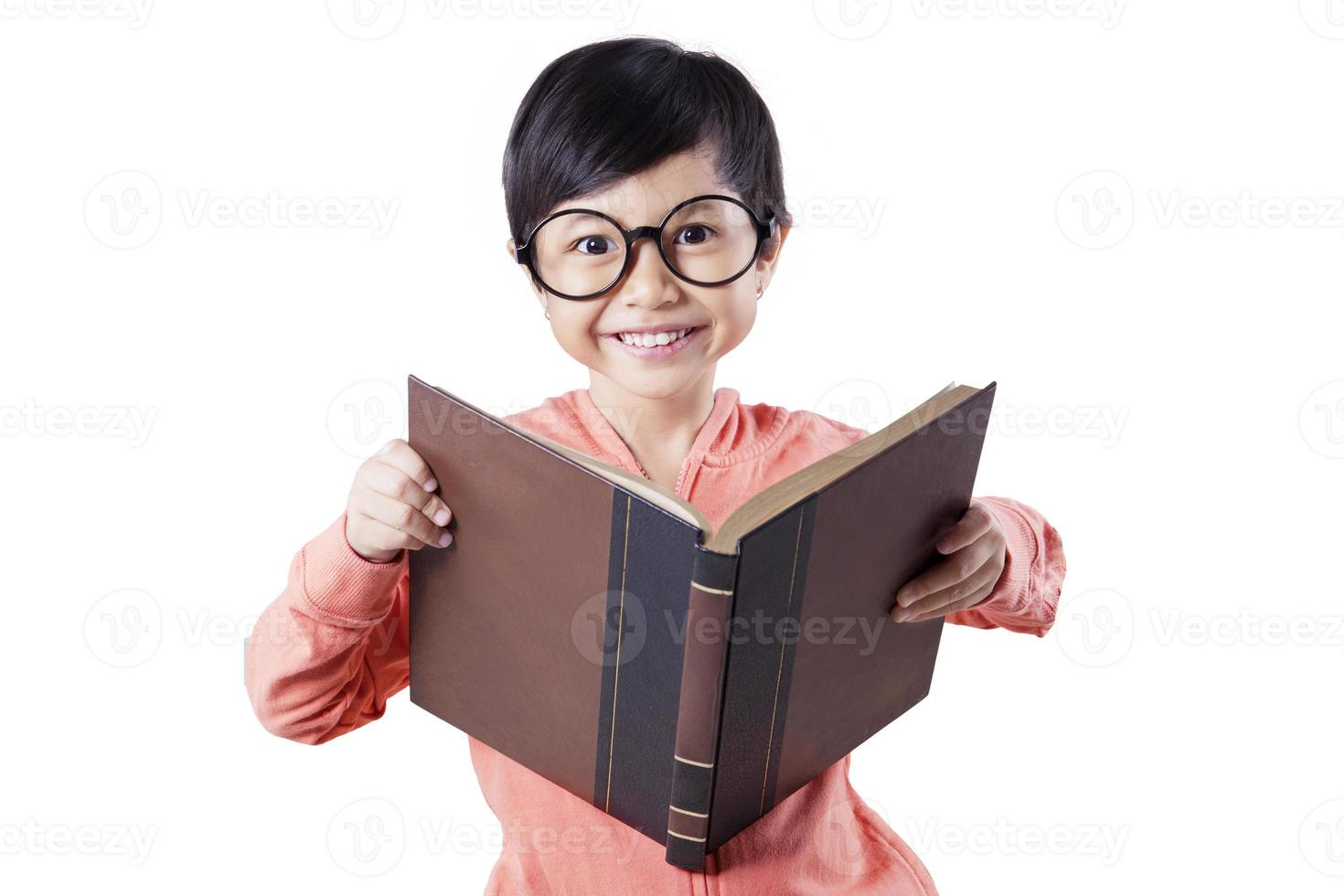 süßes Kind, das Buch im Studio liest foto