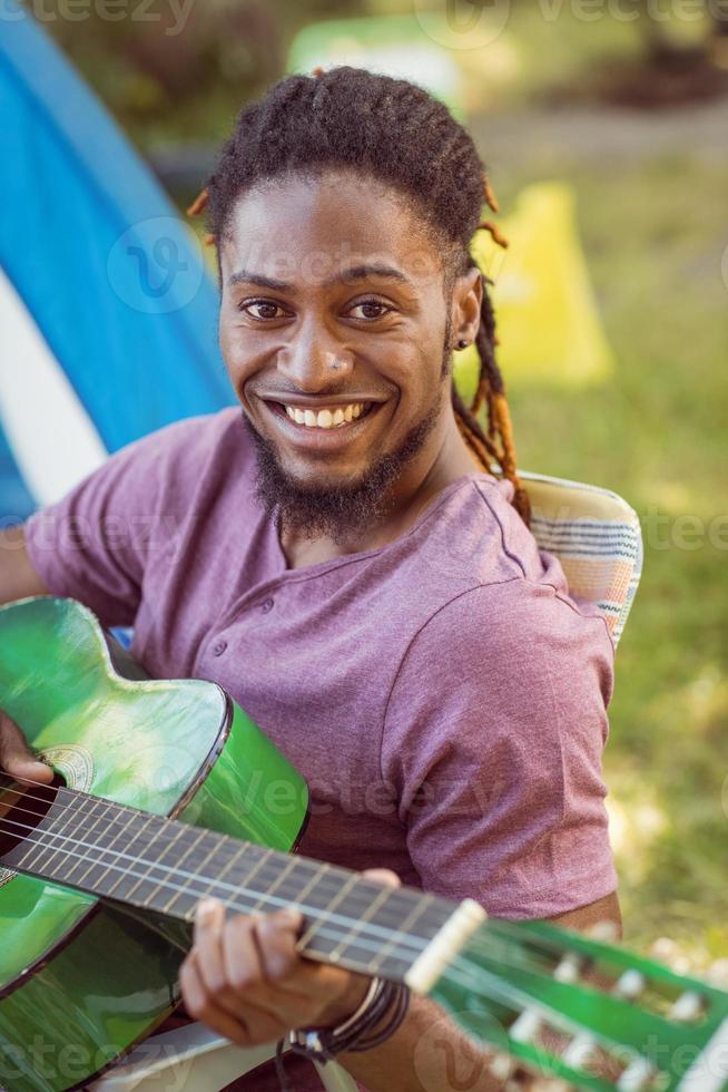 glücklicher Hipster, der an der Kamera lächelt, die Gitarre spielt foto