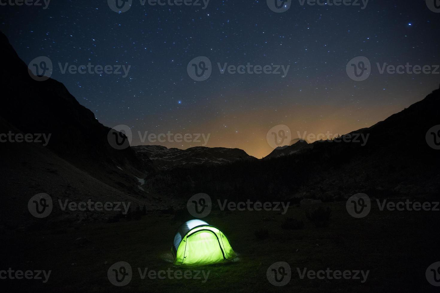 Zelt stehend auf einer Bergweide unter Sternenhimmel foto