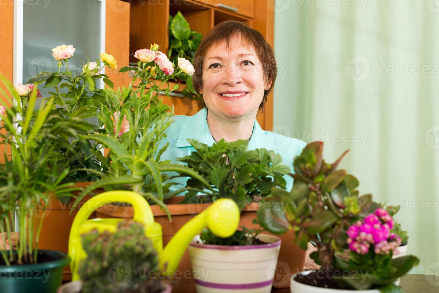 weiblicher reifer Gärtner mit lächelnden Pflanzen foto