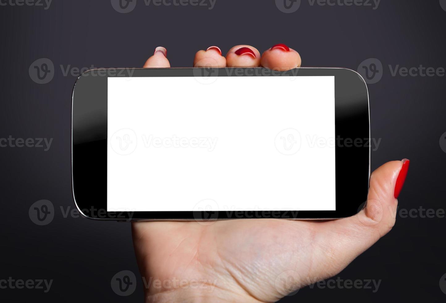 Handy in einer weiblichen Hand foto