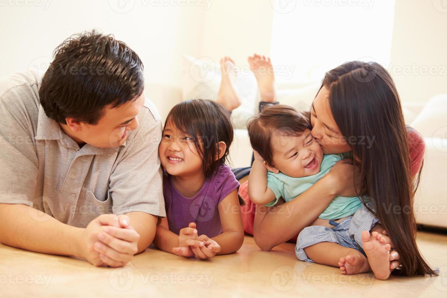 Porträt der Familie, die zu Hause auf dem Boden liegt foto