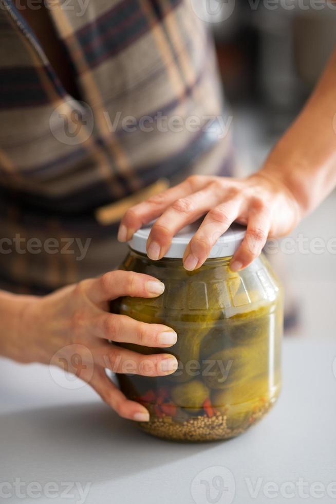 Nahaufnahme auf junge Hausfrau, die Glas mit eingelegten Gurken öffnet foto