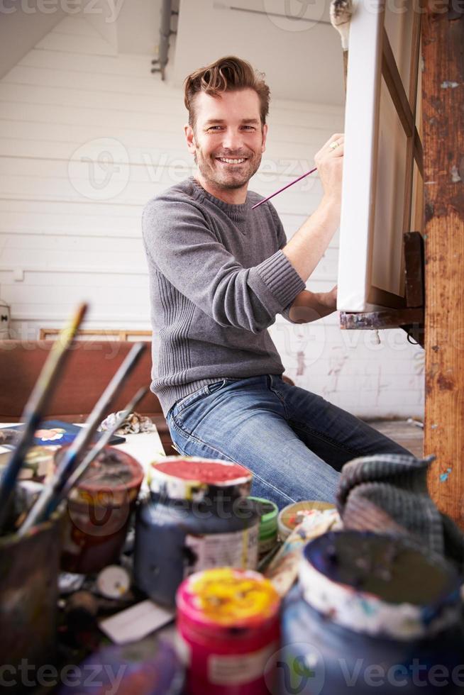 Porträt eines männlichen Künstlers, der an der Malerei im Studio arbeitet foto