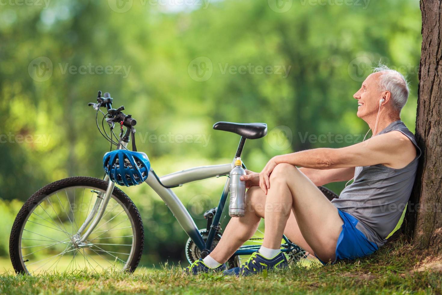älterer Radfahrer, der an einem Baum in einem Park sitzt foto